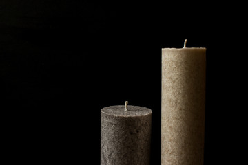 Two candles from palm wax (beige and brown) on a black background