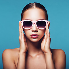 Portrait of beautiful young girl in sunglasses in studio on a blue background
