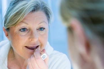 ältere frau trägt lippenstift auf
