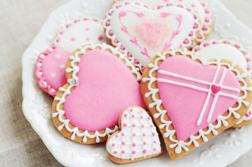 Homemade heart shaped sugar cookies with icing on white plate
