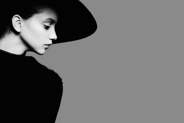 Portrait of beautiful girl in hat in profile, posing in studio, black and white photography Wall mural