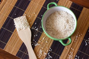 Пиала с рисом и деревянная лопатка на бамбуковом коврике
