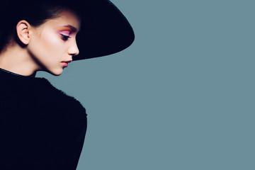 Portrait of beautiful girl in hat in profile, posing in studio
