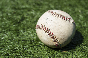 Close-up of baseball on green turf