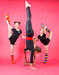 Three sporty gymnasts on red background