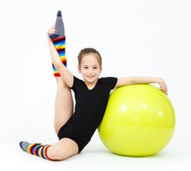 Flexible teen girl doing gymnastics exercises on fitness ball