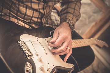 Retro style image of guitar man changing strings on electric guitar. This image has a vintage filter effect.