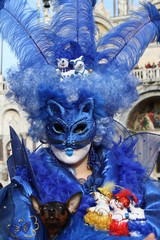 Italy, carnival mask in venice posing in san marco square. A blue cat and a little d'oggi.
