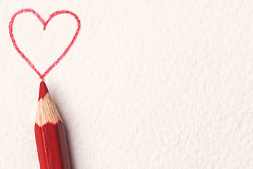 Red pencil and drawn heart over paper background