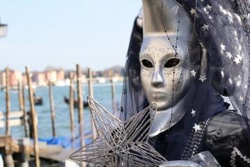 Carnival mask in Venice posing near the sea