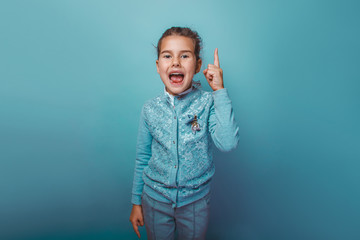 teen  girl of European appearance seven years, the idea has raised the idea a thumbs up open her mouth on a gray background