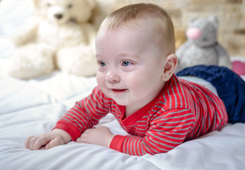 Closeup portrait view of one funny smiling cute little baby boy with blonde hair lying on bed with soft blanket looking forward