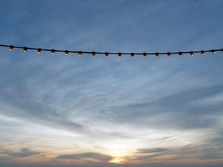 light bulbs on string wire against sunset sky