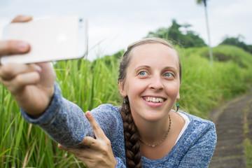 Closeup of beautiful woman taking a selfie on smart phone outdoo