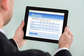 Businessman Looking At Online Survey Form On Digital Tablet