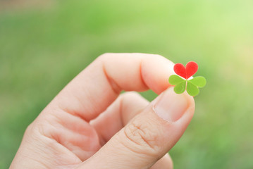 Holding red hear clover leaf for Valentine's day