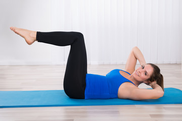 Woman Exercising In Yoga Class
