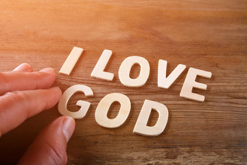 man hand spelling the word i love god from wooden letters, retro style image