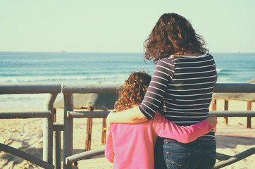 back view image of mother and child looking forward at the sea. retro style filter
