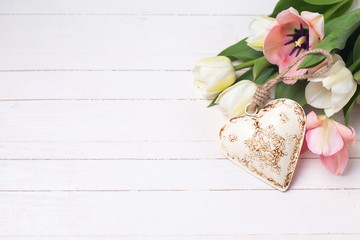 White and pink tulips flowers and decorative heart on white  pai