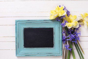 Yellow and blue spring flowers and empty blackboard   on white w