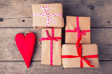 Gift boxes and red decorative heart  on  vintage wooden backgrou