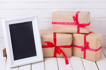 Festive gift boxes  and empty blackboard on white wooden backgro