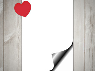 White page curl with red heart on wooden background.