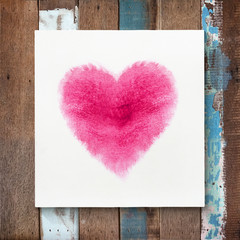 Heart shape of watercolor brushes on canvas frame with wooden ba