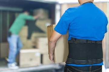 Man lift heavy carton wearing support belt for protect back
