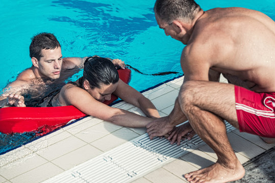 Lifeguards in training, taking victim out of the swimming pool