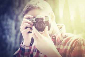 Hipster in flannel shirt taking photo with oldshool, vintage, analog camera. - retro filter