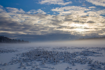 Mist over the lake with impressive clouds and sunset during the winter