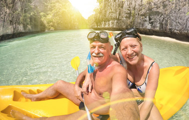 Senior happy couple taking selfie on kayak at Big Lagoon in El Nido Palawan - Travel to Philippines wonders - Active elderly concept around the world - Lens flare and sun halo are part of composition