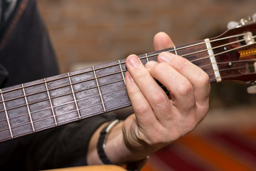 Hand playing chords on the guitar
