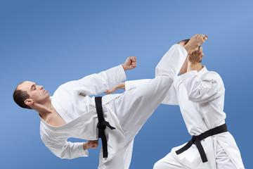 Adult athletes train kicks and blocks karate