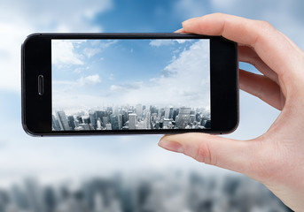 woman hand taking photo of the city with a smartphone