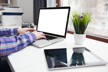 Man's hands using laptop with blank screen next to a city window