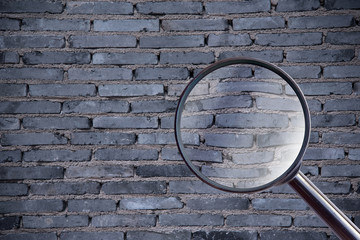 magnifying glass over brick wall