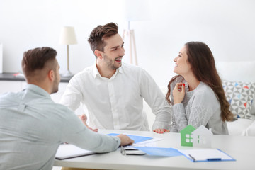 Happy family with estate agent,  in bright office