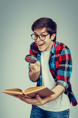 Geek with a magnifying glass and a book in hand