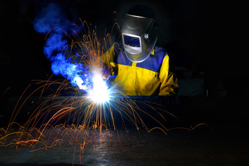 worker with protective mask welding metal.