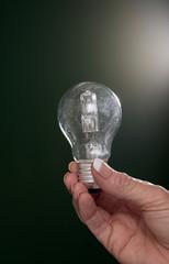 Woman's hand holding an illuminated household lightbulb