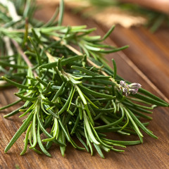 Fresh rosemary (lat. Rosmarinus officinalis) branches on dark wood, photographed with natural light (Selective Focus, Focus one third into the leaves and on the flower buds)