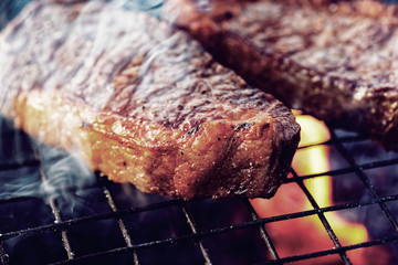 Two pieces of striploin steak on grill, toned