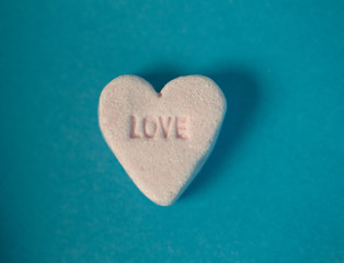 this piece of heart shaped candy with the word love printed into  it makes a good valentine stock photo