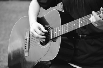 Black and white photo of guitarist playing acoustical guitar