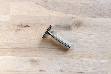 vintage chrome plated razor on a grain oak tree background seen from above