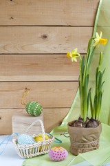 Yellow daffodil (narcissus) and in pot and handmade Happy Easter eggs on a light wooden background