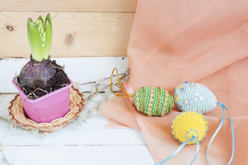 Hyacinth in pot and handmade Happy Easter eggs on a light wooden background